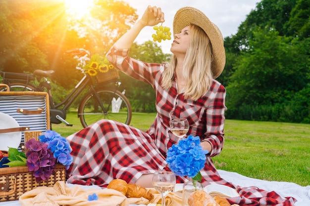 Meisje in rode geruite jurk en hoed zittend op wit gebreide picknickkleed