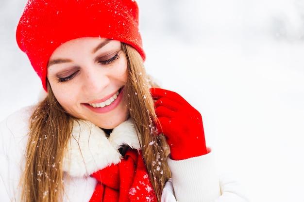 Meisje in rode hoed en sjaal glimlacht op winterdag