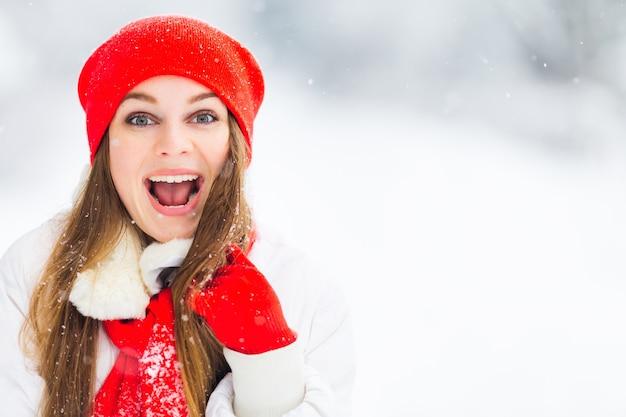 Meisje in rode hoed en sjaal kijkt in de camera en opent haar mond