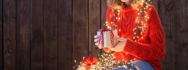 Meisje in rode hoed met kerstlicht op oude houten achtergrond