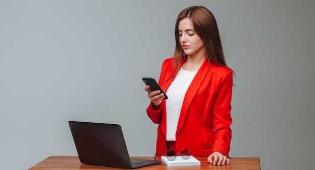 Meisje in rode jas een bericht aan het typen op de telefoon
