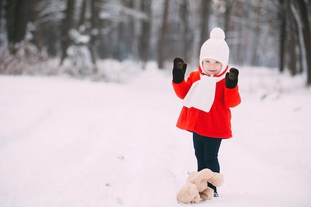 Meisje in rode jas met een teddybeer die pret op de winterdag heeft. meisje speelt in de sneeuw