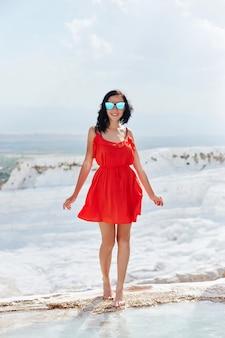 Meisje in rode jurk op witte travertijn, pamukkale