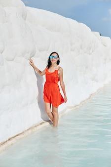 Meisje in rode jurk op witte travertijn