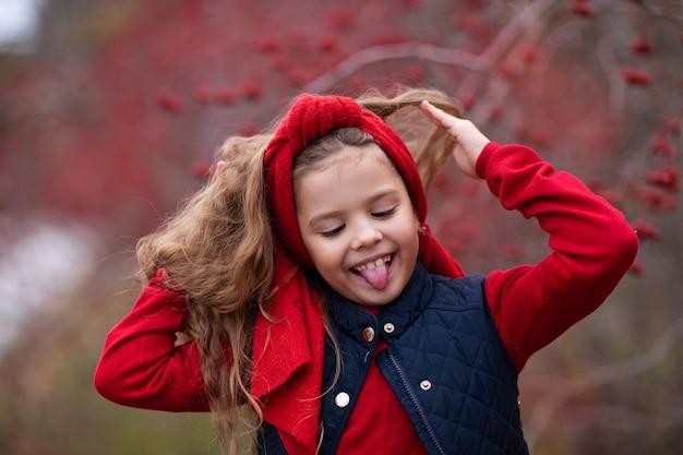 Meisje in rode outfit in herfst bos