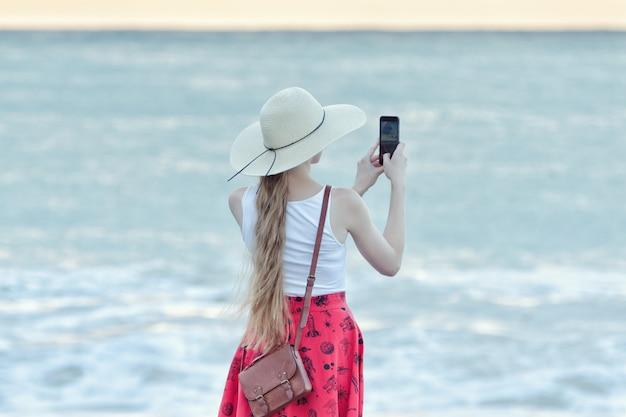 Meisje in rode rok en hoed selfie maken op het strand op zee en hemel achtergrond. achteraanzicht