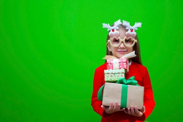 Meisje in rode tshirt in grappige bril in haar handen houdt cadeaus voor kerstvakantie nieuwjaar