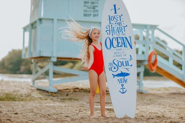 Meisje in rode zwembroek poseren op het strand met witte surfplank met citaat erop