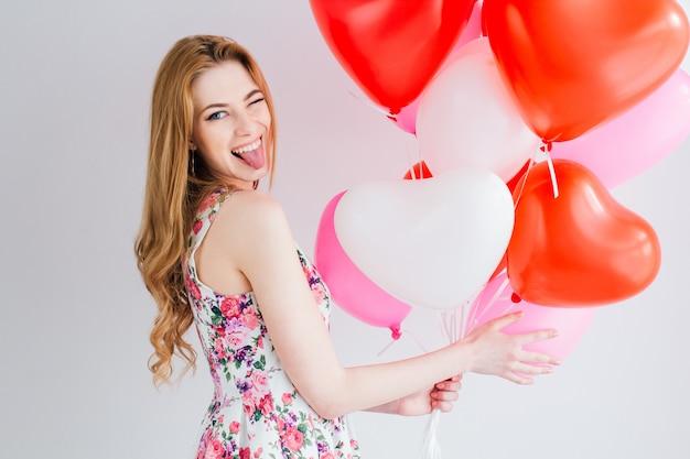 Meisje in romantische jurk met ballonnen in de vorm van een hart