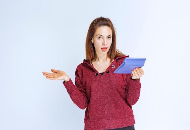 Meisje in rood jasje dat iets op een blauwe rekenmachine berekent en er verward uitziet.