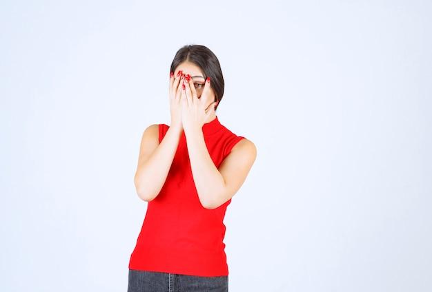 Meisje in rood overhemd dat door haar vingers kijkt.