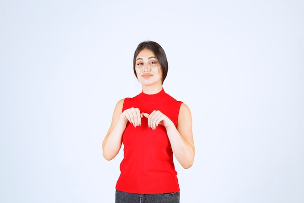 Meisje in rood overhemd dat ergens beneden wijst.