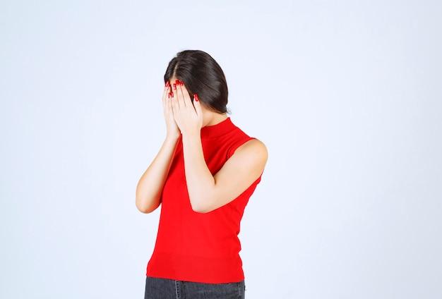 Meisje in rood overhemd dat haar hoofd met handen houdt aangezien zij hoofdpijn heeft.