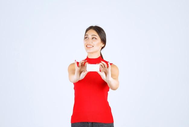 Meisje in rood overhemd dat haar visitekaartje voorstelt.