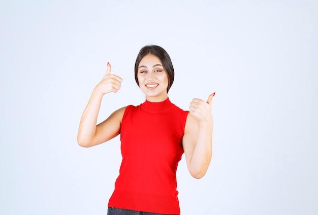 Meisje in rood overhemd dat het teken van de plezierhand toont.