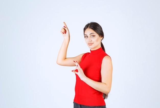 Meisje in rood overhemd dat positief handteken toont.