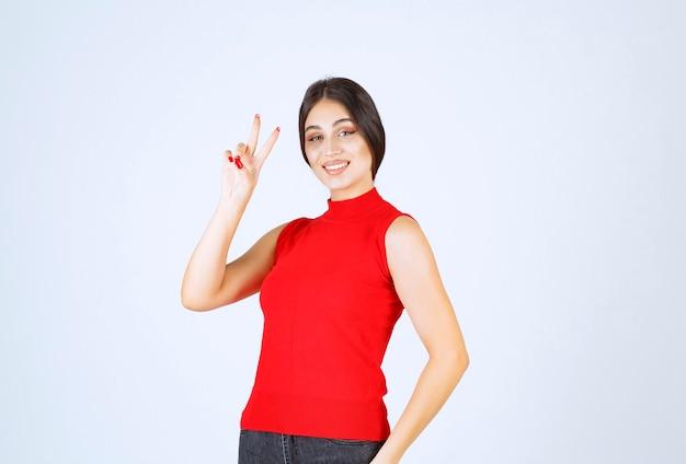 Meisje in rood overhemd dat vrede en vriendschap verzendt.