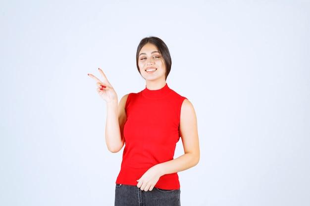 Meisje in rood overhemd dat vrede en vriendschapsteken toont.