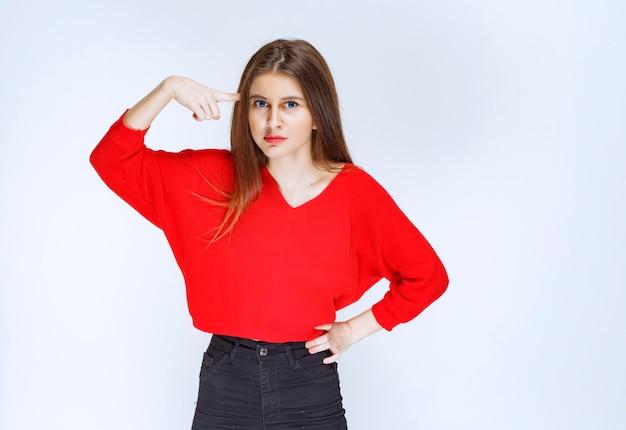 Meisje in rood overhemd denken en brainstormen.
