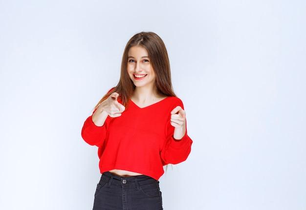 Meisje in rood overhemd die de persoon vooruit opmerken.