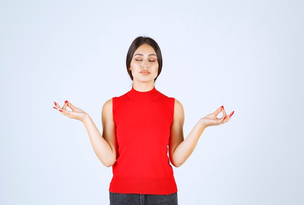 Meisje in rood overhemd die meditatie doen.