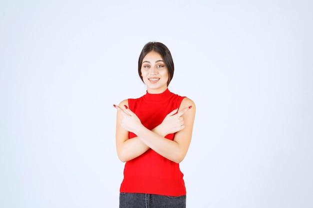 Meisje in rood overhemd wijzend naar beide kanten.