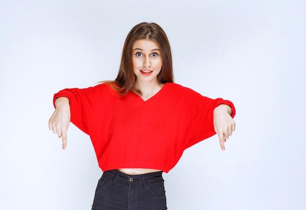 Meisje in rood overhemd wijzend op iets achter.