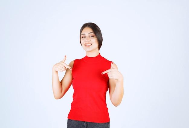 Meisje in rood overhemd wijzend op zichzelf.