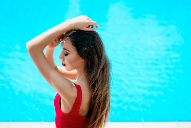 Meisje in rood pak zit bij het blauwe zwembad