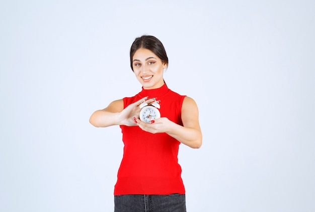 Meisje in rood shirt dat een wekker vasthoudt en promoot.