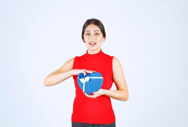 Meisje in rood shirt dat haar blauwe geschenkdoos in de vorm van een hart voorstelt.