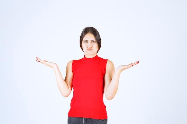 Meisje in rood shirt dat vervelend en saai gezicht maakt.