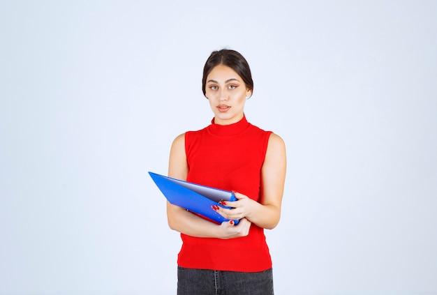 Meisje in rood shirt met een blauwe zakelijke map.