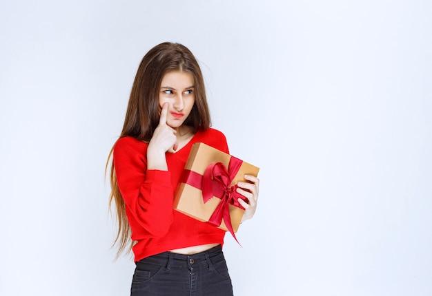 Meisje in rood shirt met een kartonnen geschenkdoos omwikkeld met rood lint en ziet er verward en attent uit.
