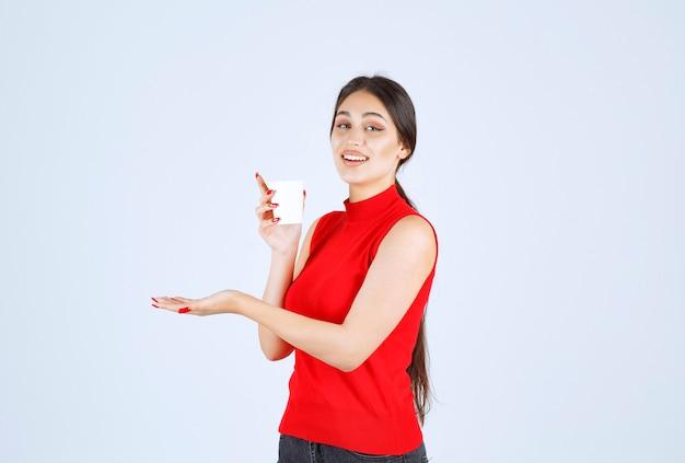 Meisje in rood shirt met een koffiekopje en ruiken.