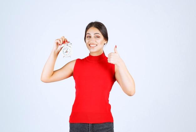 Meisje in rood shirt met een wekker en genietend van het product.