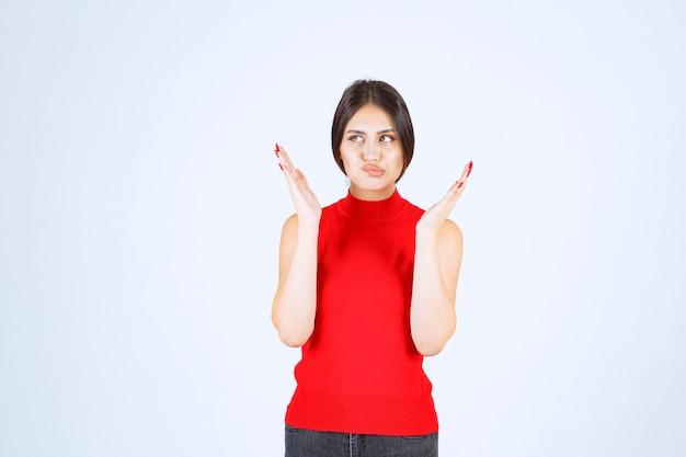 Meisje in rood shirt ziet er gestrest en nerveus uit.
