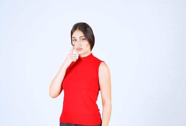 Meisje in rood shirt ziet er ontevreden uit.