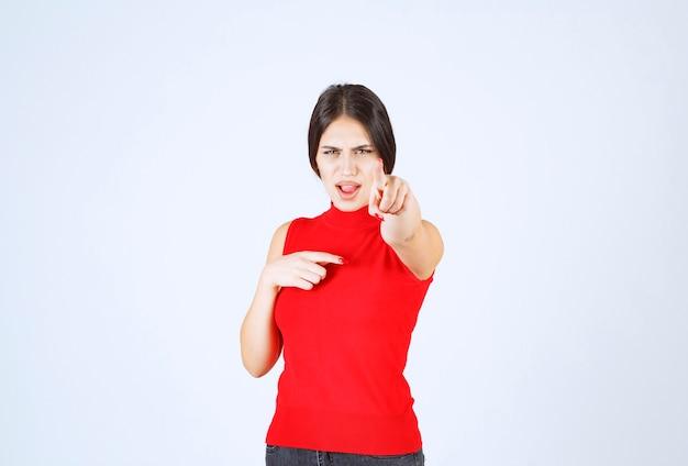 Meisje in rood shirt ziet er verdrietig en teleurgesteld uit.