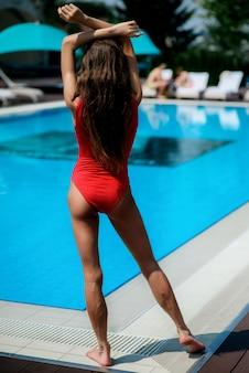Meisje in rood zwembroek staat bij het blauwe zwembad