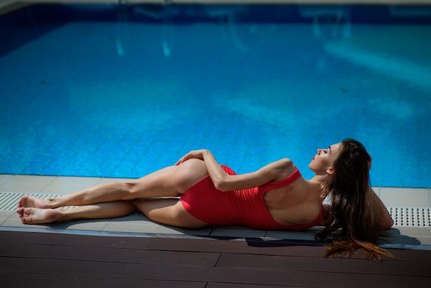 Meisje in rood zwempak ligt bij het blauwe zwembad