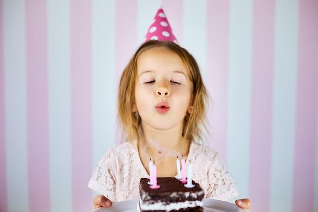 Meisje in roze glb die kaarsen op een cake van de verjaardagschocolade op haar verjaardagspartij thuis uitblazen. portret verjaardag kind.
