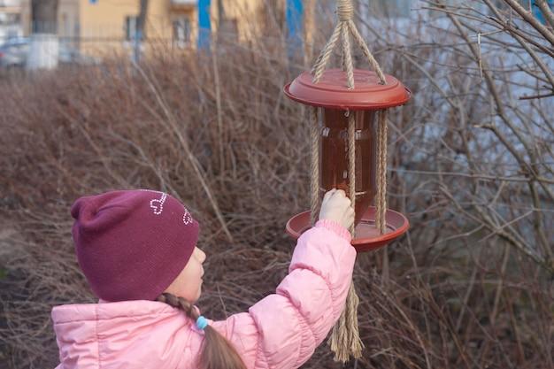 Meisje in roze jas en hoed giet vogelvoer in het voer.