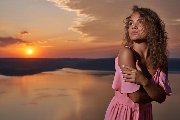 Meisje in roze kleding op zonsondergang als achtergrond en meer.