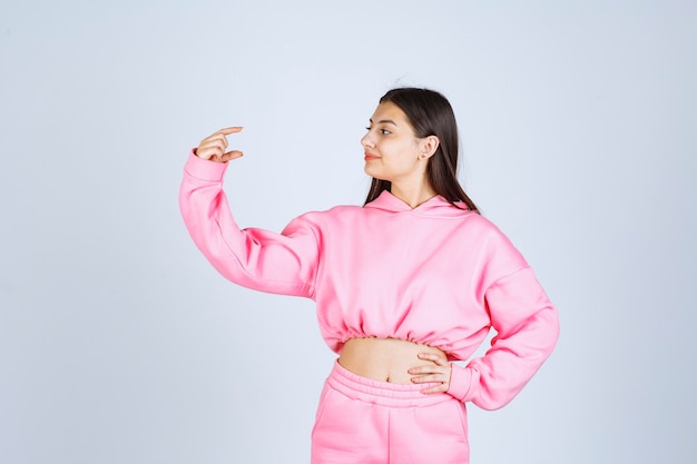 Meisje in roze pyjama dat de hoeveelheid van een product toont