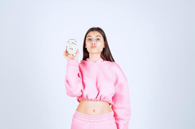 Meisje in roze pyjama die een wekker vasthoudt en deze promoot als product.