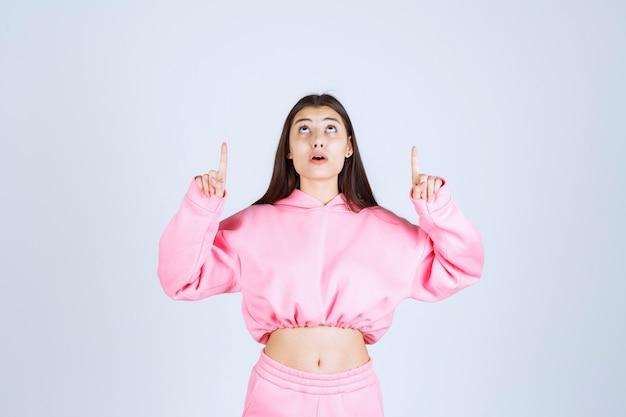 Meisje in roze pyjama die naar ergens wijst.