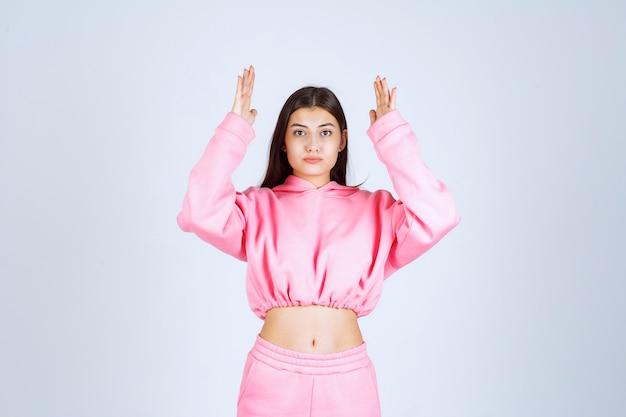 Meisje in roze pyjama met de geschatte hoeveelheid of maat van een product