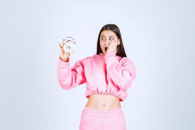 Meisje in roze pyjama met een wekker en beseft dat ze te laat is.