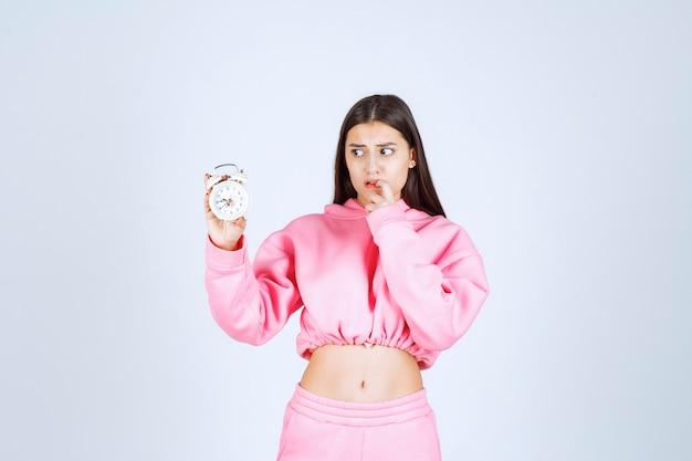 Meisje in roze pyjama met een wekker en ziet er bedachtzaam en verward uit.